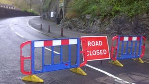 Road closed sign and barrier across the main road in Cheddar