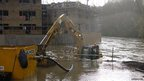 A half-submerged digger on a building site in Bradford-on-Avon, near Bristol