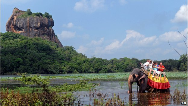 Tourists on an elephant with the ancient historic rock fortress of Sigiriya in the background