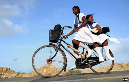 Schoolgirls ride a bicycle in Jaffna