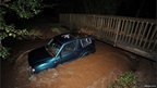 An empty car wedged against a footbridge in a river swollen with muddy water.