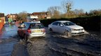 Two cars pass each other in sunny weather on a road covered in shallow flood water.