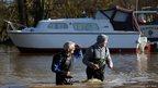 Men walking through floodwater
