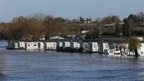 A field of static caravans in flood water which reaches the bottom of their doors.