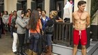 A lifeguard model stands outside the front door of a Hollister Co. clothing store, as consumers line up in the early morning hours in Glendale, California, on 23 November 2012