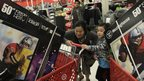 A woman and her daughter push a heavy shopping cart at Target on the Thanksgiving Day holiday in Burbank, California, on 22 November 2012