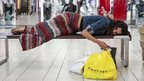 Jasmine Britton, 18, of Huntington Beach rests while shopping at the Los Cerritos Center mall on Black Friday in Cerritos, California, on 23 November 2012