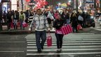 People carry shopping bags as they walk through Herald Square in New York on 23 November 2012