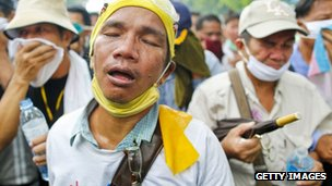 Protesters react to tear gas fired by Thai police during anti-government rally in Bangkok