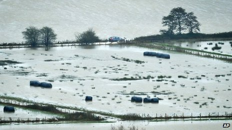 A vehicle manages to drive along a road between flooded land in Somerset 