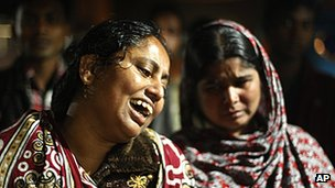 Bangladeshi women react outside the clothes factory