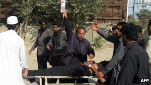 A wounded victim is carried to hospital after a bombing in Dera Ismail Khan (25 Nov 2012)