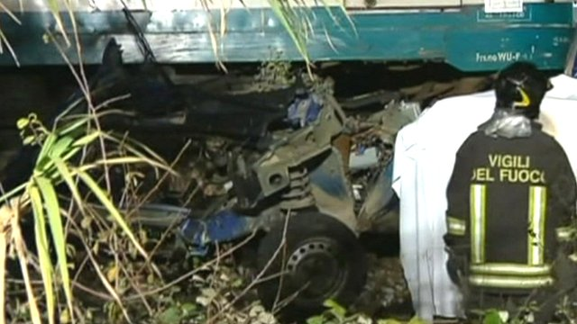 Car wreckage trapped under train