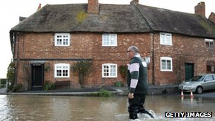 A man wades through floodwaters in Tewkesbury