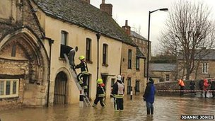 Firefighters enter a flooded property