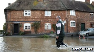 A man wades through floodwaters in Tewkesbury, in Gloucestershire