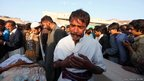 A man mourns the death of his relatives during a funeral for the victims of a suicide bomb blast, in the outskirts of the Pakistani city of Rawalpindi