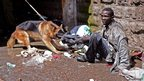 A man is restrained by a policeman's dog in the Somali district of Eastleigh in Nairobi
