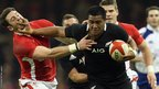 New Zealand's Julian Savea hands off Wales' Alex Cuthbert as the home side struggle to contain the superior visitors