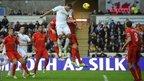 Swansea City captain Ashely Williams rises to meet Jonathan de Guzman's corner but Liverpool midfielder Joe Allen clears off the line
