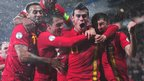 Gareth Bale is mobbed by his Wales team-mates after his two goals see them come from behind to beat Scotland in a World Cup qualifier in Cardiff