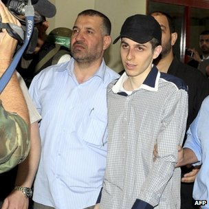 File picture from 18 October 2011 shows Israeli soldier Gilad Shalit (R) being escorted by Ahmed Jaabari, upon his arrival at the Egyptian side of the Rafah border