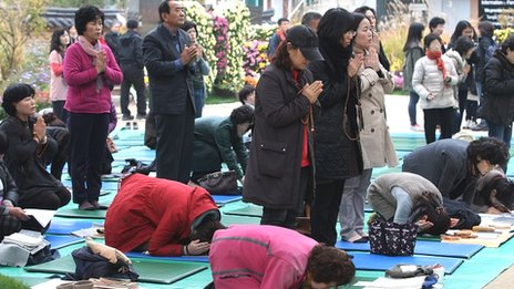 Parents in South Korea, earlier this month, pray for their children's