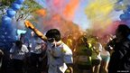 A runner throws paint powder at the starting line of the Kolorfest race in San Salvador