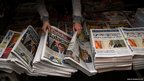 A newspaper vendor arranges local newspapers featuring the results of the Catalan elections in Barcelona