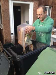 A Kennford resident throwing out rotten food after flooding
