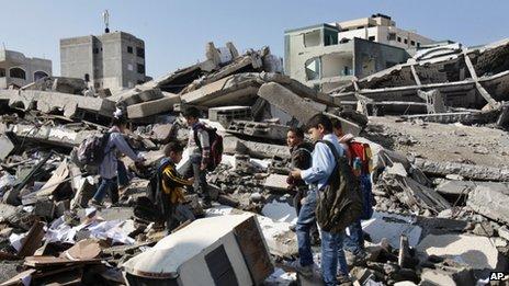 Palestinian school children walk in the rubble left days after an Israeli strike destroyed the Hamas interior ministry in Gaza City