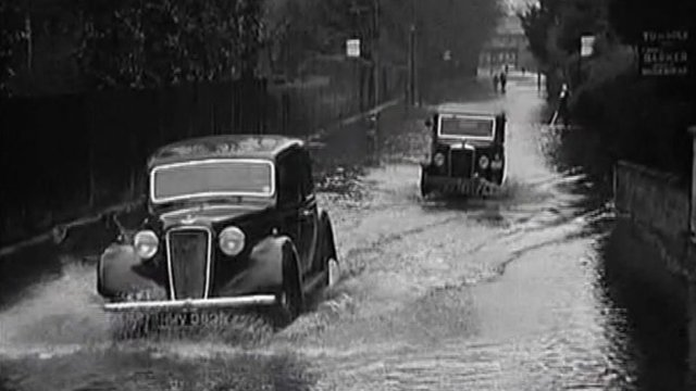 Vintage cars drive through floods