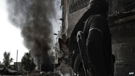 A rebel fighter looks at smoke billowing from a burning bus in Aleppo (28 October 2012)
