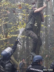 A riot police officer sprays tear gas at a protester up a tree