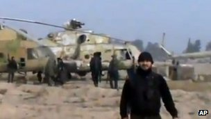 Screengrab of video published by opposition activists purportedly showing rebel fighter standing near helicopters at an airbase near Damascus (25 November 2012)