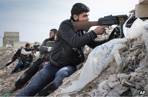 Syrian rebel fighters take aim near the Damascus-Aleppo highway in Maarat al-Numan (17 November 2012)