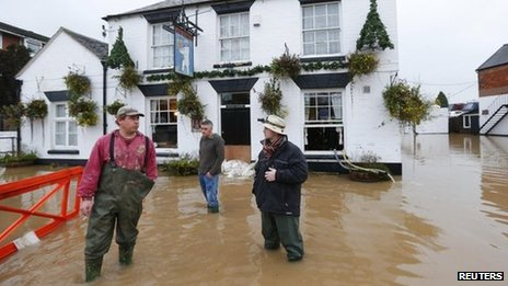 People stand in flood water outside the White Bear pub in Tewkesbury