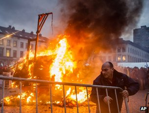 A farmer moves a barrier as a trailer burns in Brussels, 26 November