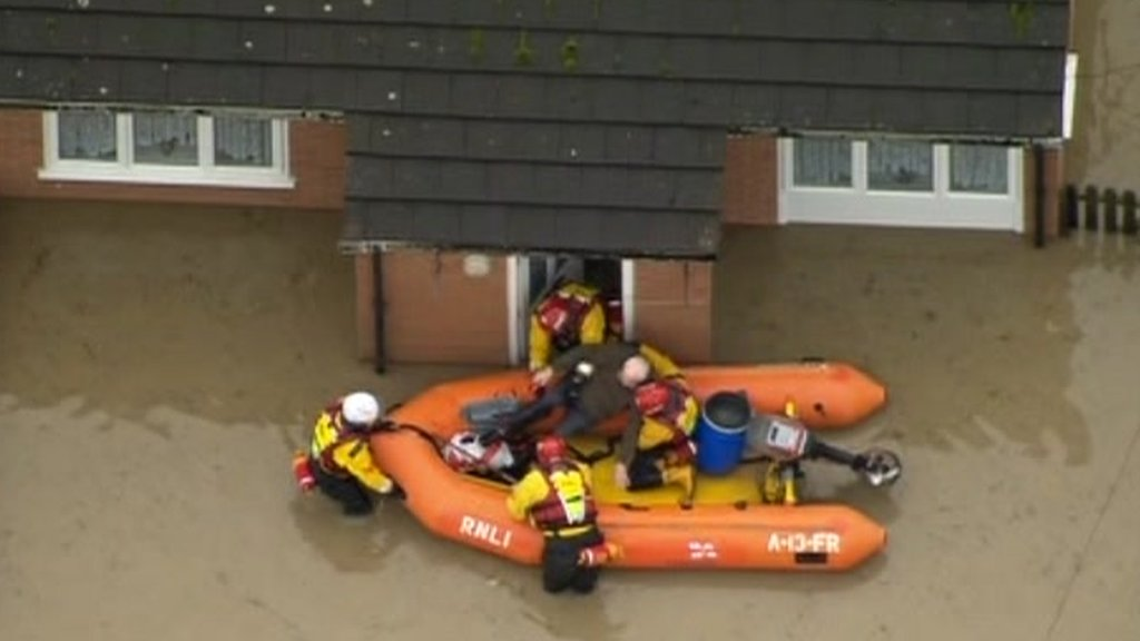 Rescue boat helping someone from their flooded house