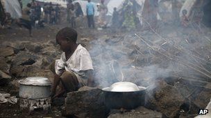 An internally displaced Congolese child heats water at the Mugunga camp outside the eastern town of Goma, Saturday 24 November 2012