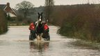 Two men on a horse in flooded water