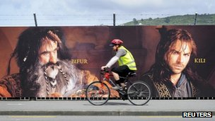 Man cycles past sign board in Wellington, New Zealand, advertising The Hobbit, on 27 November 2012