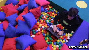 A man sits in a ball pit, typing on a laptop