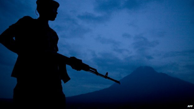 A militia soldier in eastern DR Congo on guard with a volcano in the background (Archive shot February 2008)