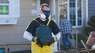Man dressed in protective clothing empties his home