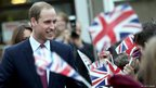 Prince William, Duke of Cambridge, smiles as pupils cheer and wave Union Flags as he arrives at Manor School in Cambridge