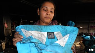 A union official hold a pair of trousers from Sean Combs ENYCE line at the burnt-out Tazreen factory