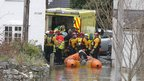 Ambulance workers load a stretcher into an ambulance as lifeboat crews look on in a flooded street in St Asaph
