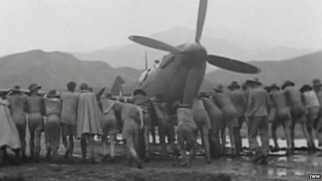 Men push spitfire along ground