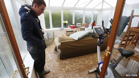 James Evans looks at muddy sediment left after water receded from his home in St Asaph